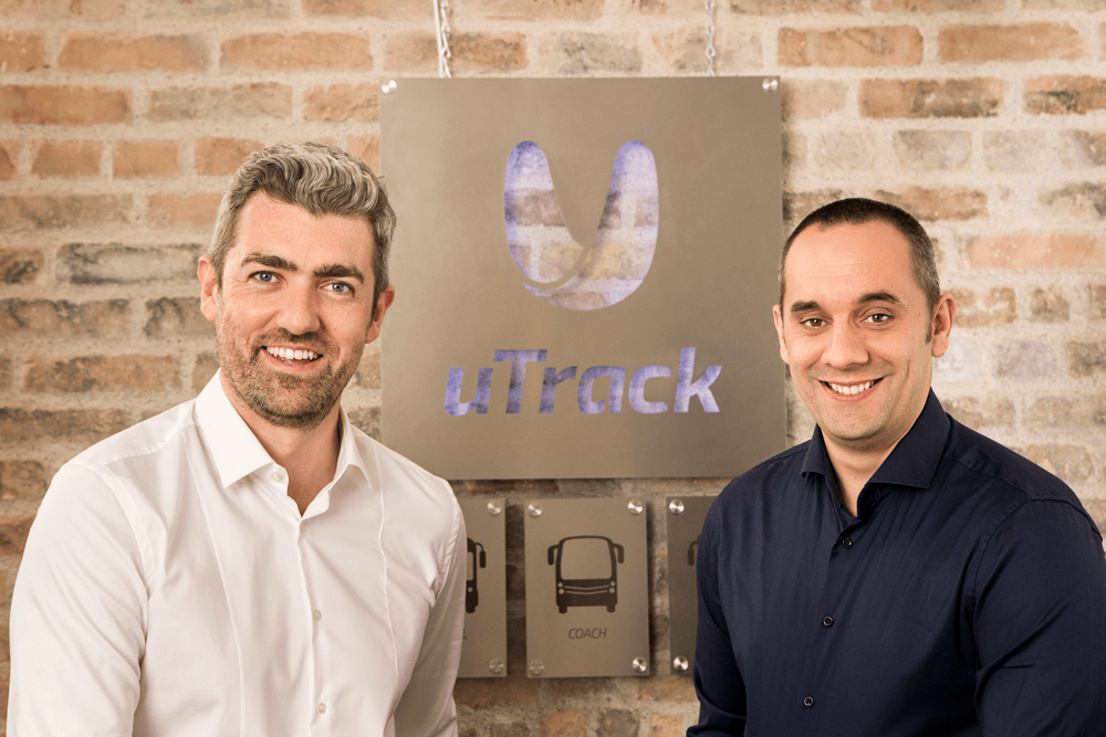Photo of uTrack founders Eamon and Conor beside each other with the backlit uTrack sign